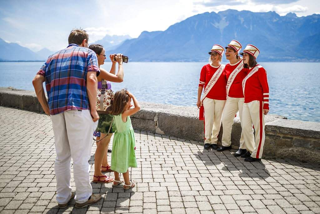 People in costumes pose for photos at the Fete des Vignerons parade during the official opening parade in Vevey, Switzerland, which is on until August 11. (Valentin Flauraud/Keystone via AP)