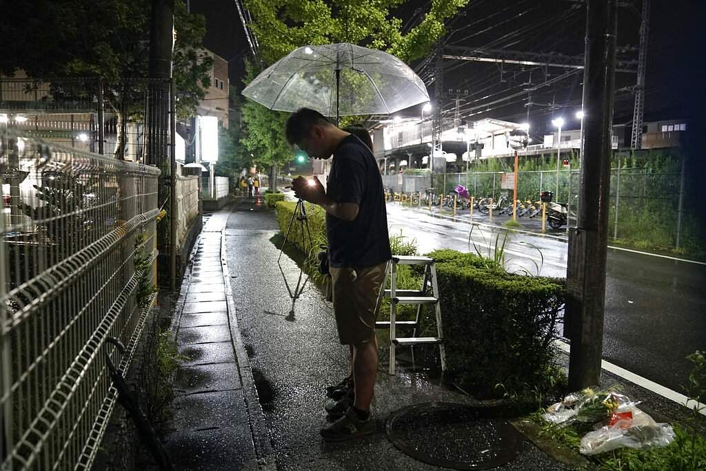 A couple prays after placing flowers near the Kyoto Animation building in Kyoto, Japan. (AP Photo/Jae C Hong)