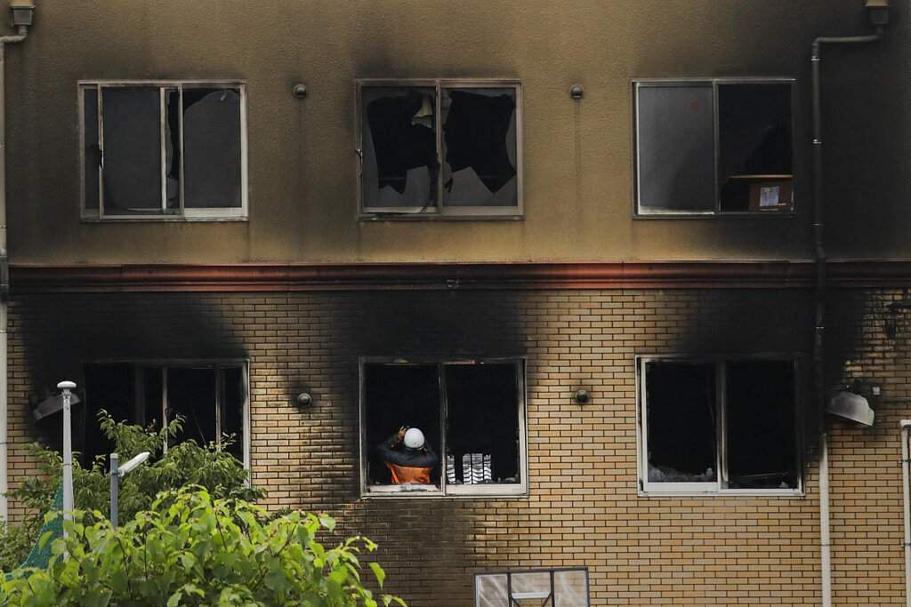 An investigator takes pictures inside the Kyoto Animation Studio building destroyed in an arson attack, in Kyoto, Japan. (AP Photo/Jae C Hong)