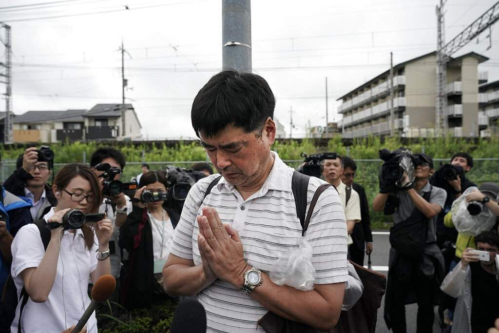 A man prays for the victims of Thursday's fire at the Kyoto Animation Studio building, in Kyoto, Japan. (AP Photo/Jae C Hong)
