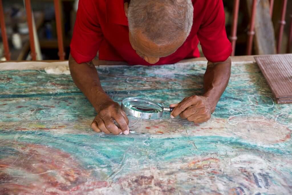Franck Louissaint works on the painstaking renovation of a painting by Haitian artist Robert Saint Bruce at the Musée d'Art du Collège Saint Pierre. (AP Photo/Dieu Nalio Chery)