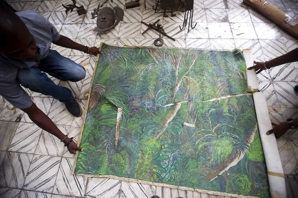 Clautaire Leveille and a worker roll up an quake-damaged painting by Haitian artist Jean-Claude Toussaint at Musée d'Art du Collège Saint Pierre, in Port-au-Prince, Haiti. (AP Photo/Dieu Nalio Chery)