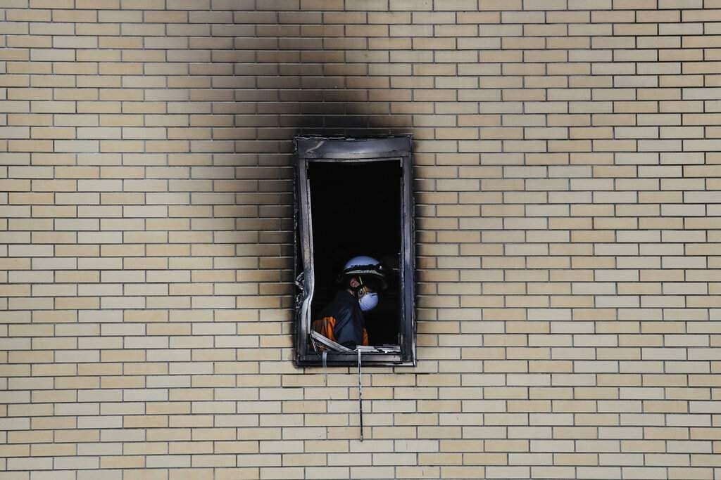 A firefighter is seen through the window of the Kyoto Animation Studio building consumed in an arson attack, in Kyoto, Japan. (AP Photo/Jae C Hong)