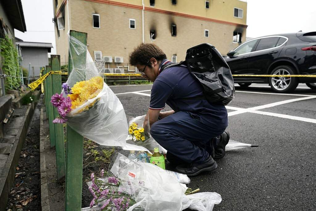 A man places flowers outside the Kyoto Animation Studio building consumed in an arson attack, Friday, July 19, 2019, in Kyoto, Japan. (AP Photo/Jae C Hong)