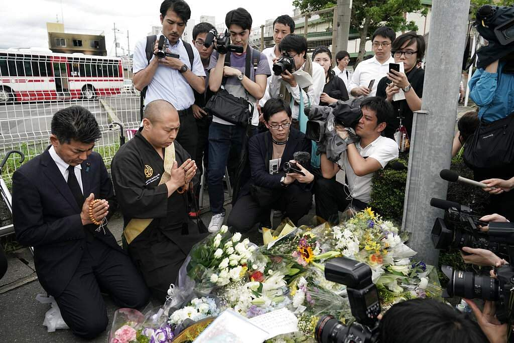 Japanese Diet member Kenta Izumi and Buddhist monk Matsumoto Genkun pay respects at a makeshift memorial site in front of burned Kyoto Animation Studio building, in Kyoto, Japan. (AP Photo/Jae C Hong)