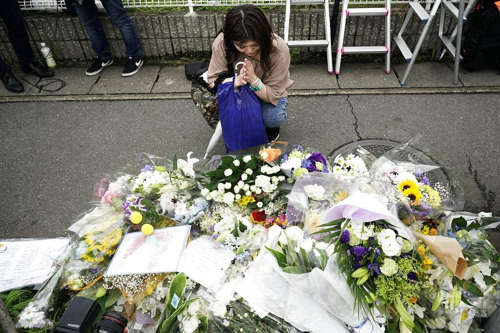 A woman prays to honour the victims of Thursday's fire at the Kyoto Animation Studio building, in Kyoto, Japan. (AP Photo/Jae C Hong)