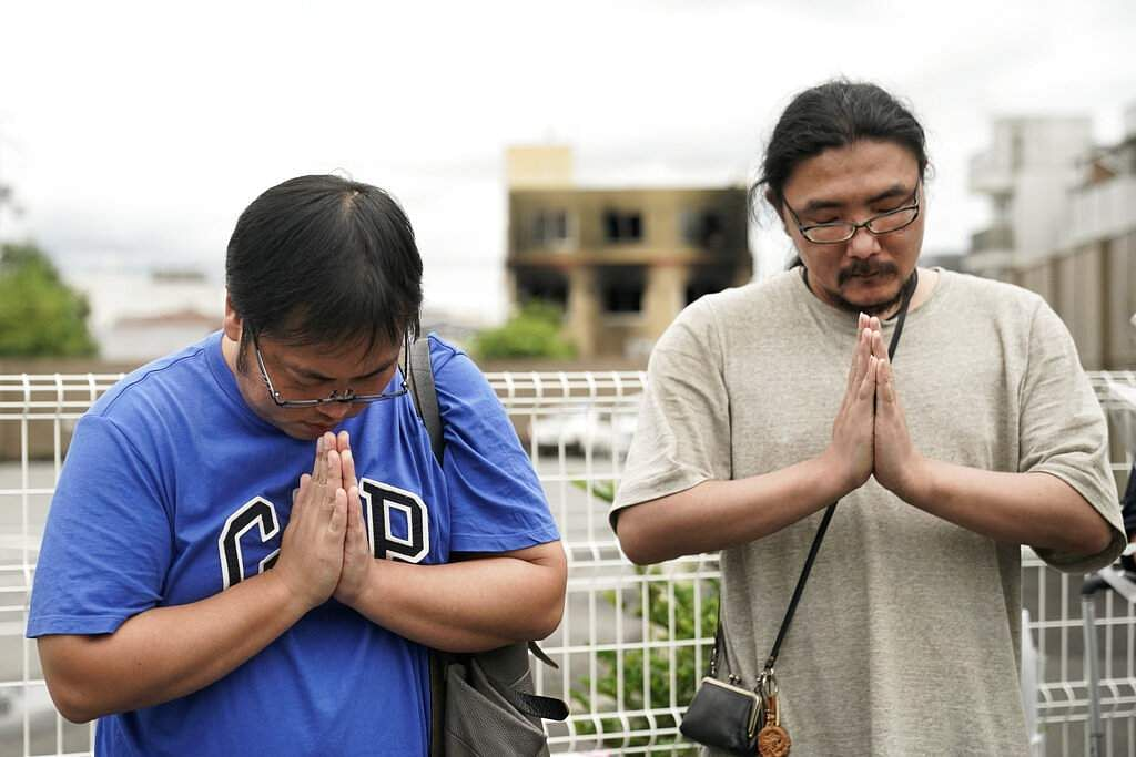Two men pay respects at a makeshift memorial site to honour the victims of Thursday's fire at the Kyoto Animation Studio building, in Kyoto, Japan. (AP Photo/Jae C Hong)