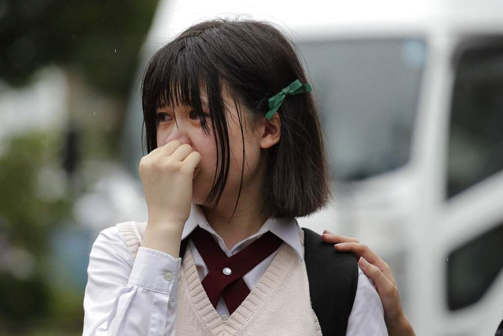 A woman sheds tears as she visits a makeshift memorial honoring the victims of Thursday's fire at the Kyoto Animation Studio building, in Kyoto, Japan. (AP Photo/Jae C Hong)