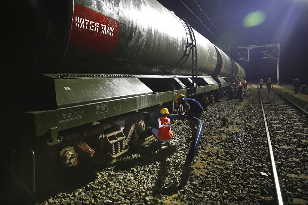 Workers decant water from a train at Villivakkam railway station in Chennai. Chennai's water board employs an army of trucks to deliver 500 million litres of water every day. (AP Photo/Manish Swarup)