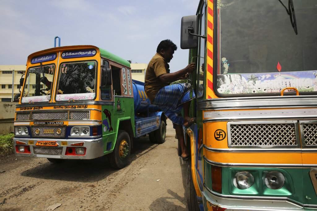 Water tanker driver Ranganathan climbs onto his vehicle at a water filling depot in Chennai. (AP Photo/Manish Swarup)