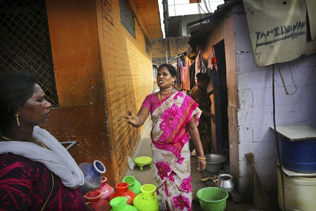 K Devi, 41, talks to her neighbour as they wait for a water truck to arrive in their shanty town in Chennai. Devi at times supplements her supplies with cans for Rs 35 apiece. (AP Photo/Manish Swarup)