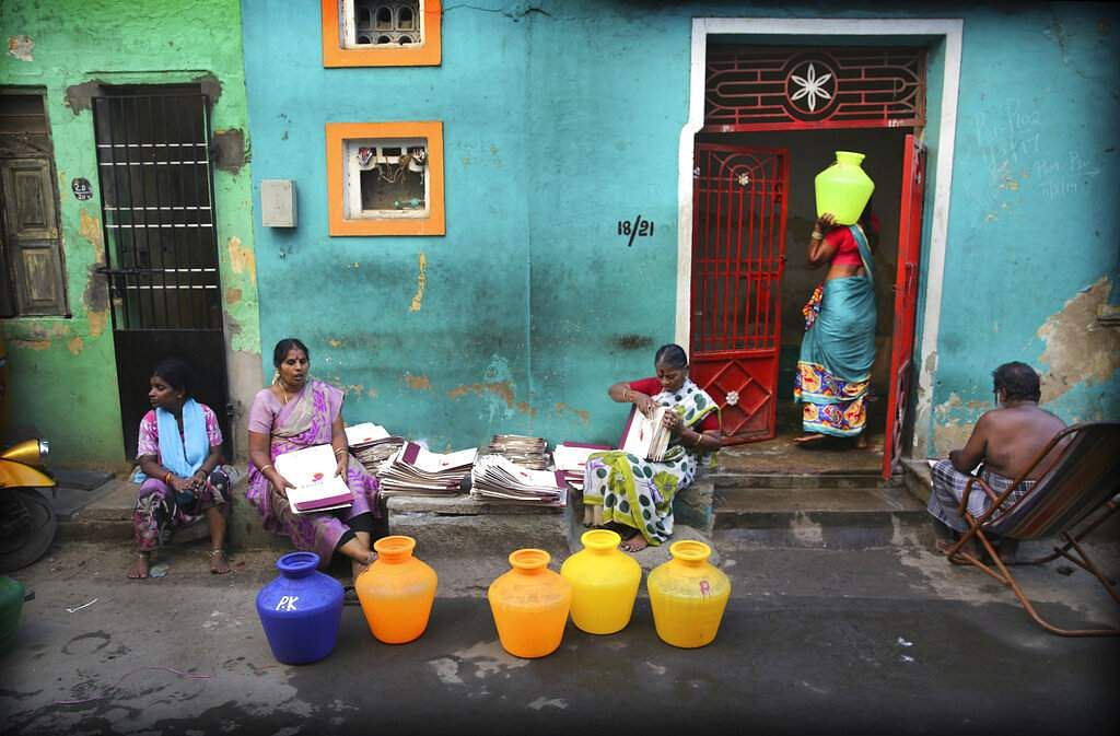A woman walks into a house with a vessel of drinking water filled from a water truck in Chennai. (AP Photo/Manish Swarup)
