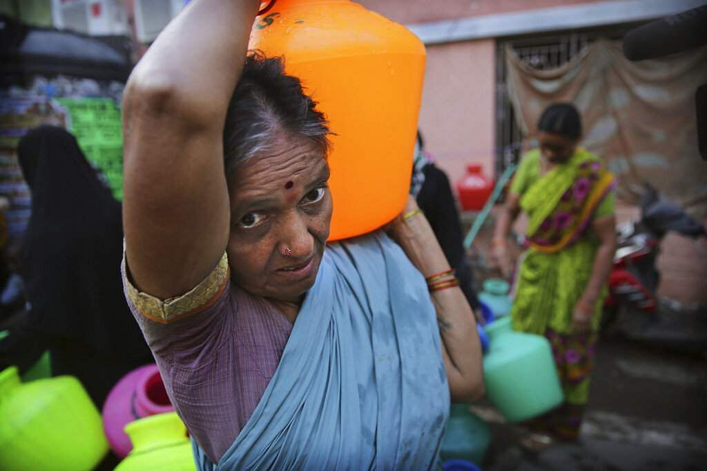 An elderly woman carries drinking water filled from a water truck in Chennai. (AP Photo/Manish Swarup)