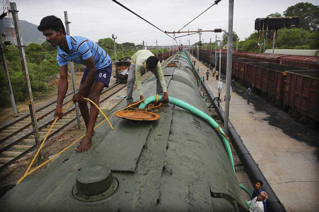 Workers fill a train with water piped in from Mettur dam on River Cauvery, at Jolarpet. The 50-tank train carries 2.5 million litres of water on its daily sojourns. (AP Photo/Manish Swarup)