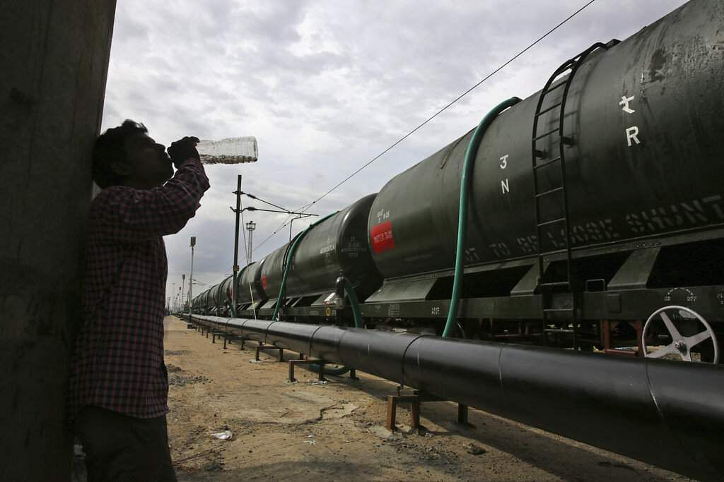 A worker takes a break as train wagons are filled with water at Jolarpet railway station. The 50-tank train carries 2.5 million litres of water on its daily sojourns. (AP Photo/Manish Swarup)