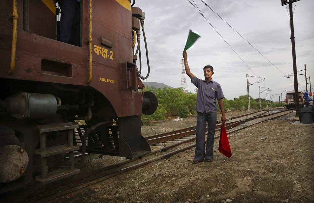 A railway guard clears the track for a train carrying drinking water, at Jolarpet railway station. The 50-tank train carries 2.5 million litres of water on its daily sojourns. (AP Photo/Manish Swarup)