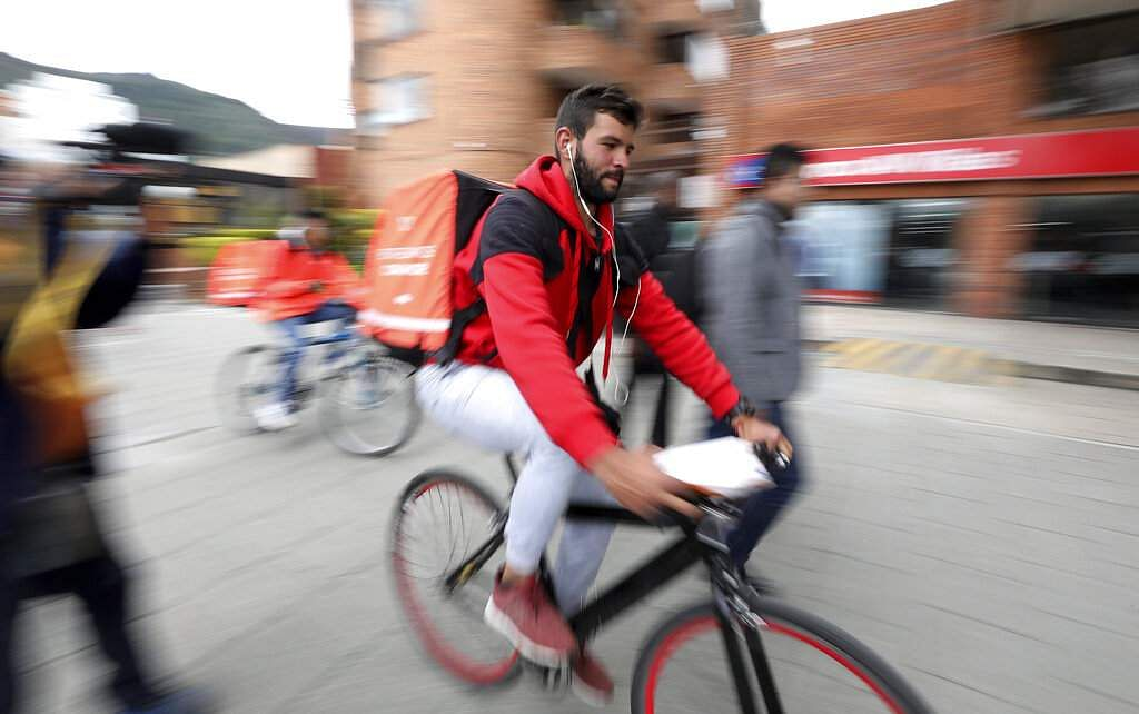 Venezuelan courier Samuel Romero, 21, takes an order to a Rappi customer on his bicycle in Bogota, Colombia. (AP Photo/Fernando Vergara)
