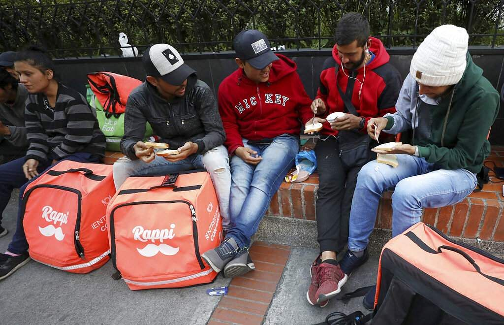 Venezuelan bicycle courier Samuel Romero and fellow Venezuelan couriers make sandwiches as they wait for delivery orders through Rappi in Bogota. (AP Photo/Fernando Vergara)