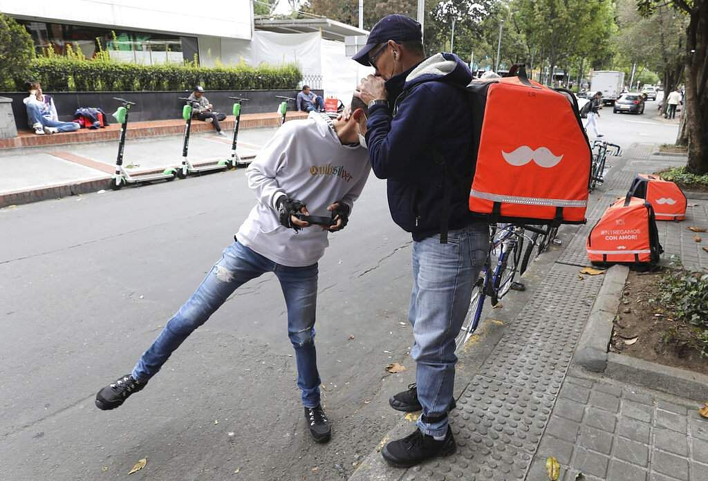 Venezuelan bicycle courier Luis Tarre, 60, kisses the head of his 20-year-old son Raul as they wait for Rappi delivery orders in Bogota. (AP Photo/Fernando Vergara)
