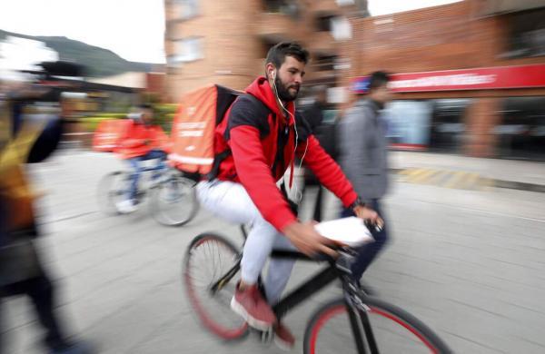 Venezuelan courier Samuel Romero, 21, takes an order to a Rappi customer on his bicycle in Bogota, Colombia. (AP Photo/Fernando Vergara)
