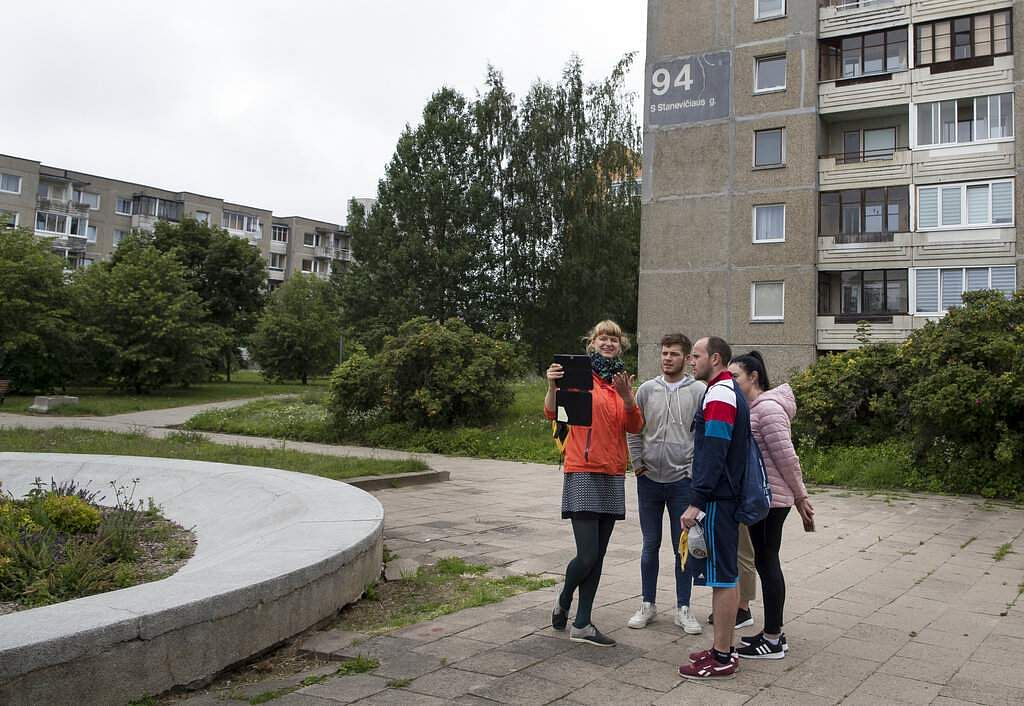 A tour guide shows a group of tourists where the series Chernobyl was filmed in Vilnius, Lithuania. The HBO series is helping Lithuania grow as a tourist destination. (AP Photo/Mindaugas Kulbis)