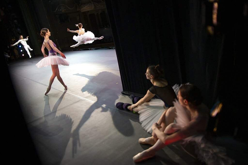 Two ballerinas rest as other dancers perform during a rehearsal in the Bolshoi Theater in Moscow, Russia. (AP Photo/Alexander Zemlianichenko)