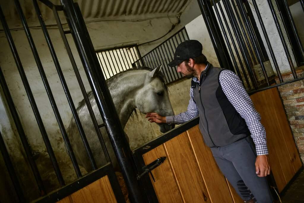 Roberto Armendariz pets one his horses inside a stable, at his ranch in Noain, northern Spain. (AP Photo/Alvaro Barrientos)