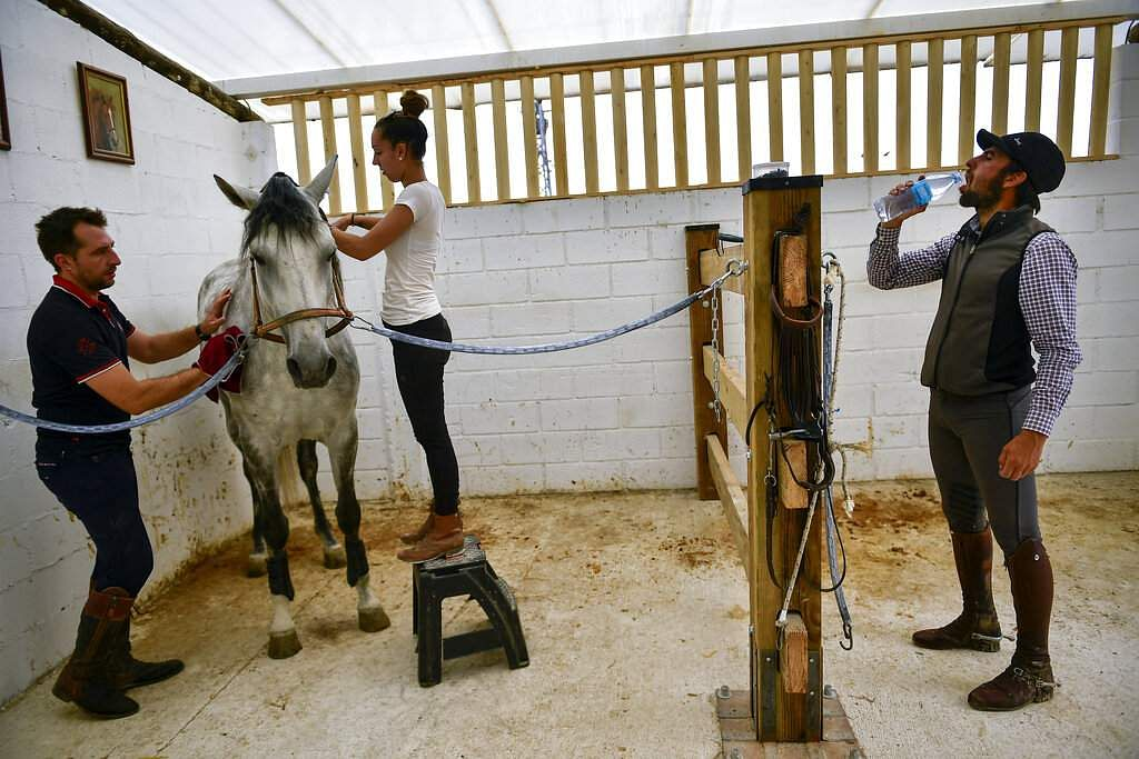 Roberto Armendariz drinks water while his assistants, Leyre Gonzalez and Jose Aguirre prepare a horse for training at his ranch in Noain, northern Spain. (AP Photo/Alvaro Barrientos)