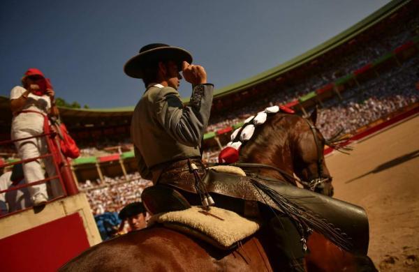 Roberto Armendariz, 33, Spanish 'rejoneador' or mounted bullfighter, enters the bullring for a horseback bullfight at San Fermin Fiestas, northern Spain. (AP Photo/Alvaro Barrientos)