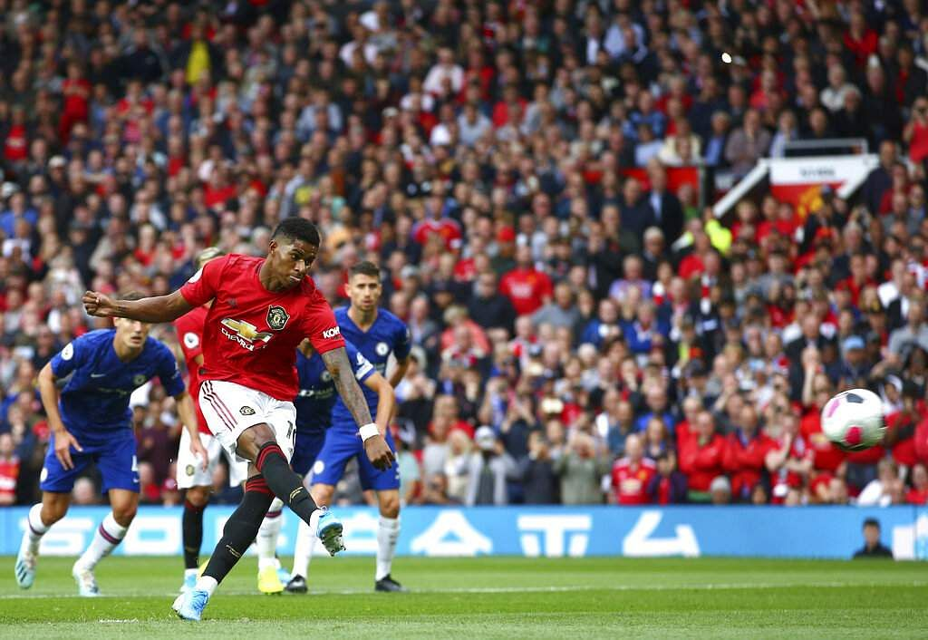 Marcus Rashford shoots a penalty to score in the EPL soccer match at Old Trafford. Maguire, who completed his 80 million pound transfer from Leicester, was man-of-the-match. (AP Photo/Dave Thompson)