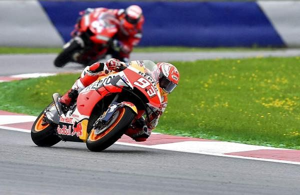 Spain's Marc Marquez of Repsol Honda followed by Italian Andrea Dovizioso of Ducati during a warm up session at the Austrian motorcycle Grand Prix in Spielberg, Austria. (AP Photo/Kerstin Joensson)