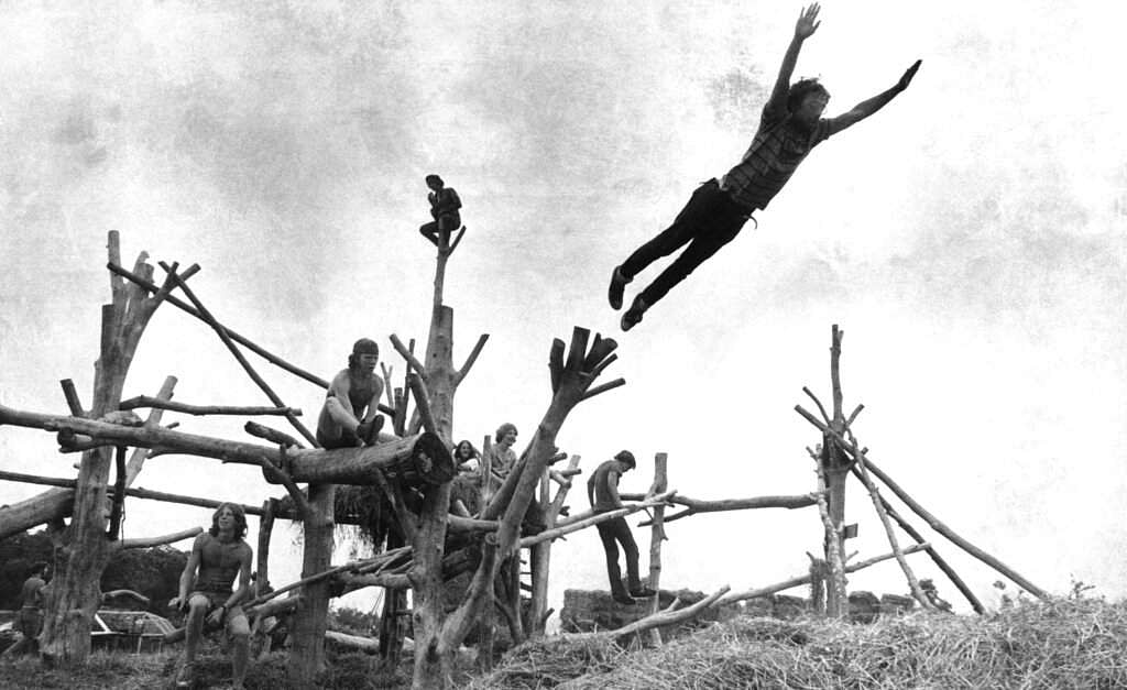 1969 file photo: Rock music fans sit on a tree sculpture as one leaps mid-air onto a pile of hay during the Woodstock Music and Art Festival held in Bethel, NY. (AP Photo)