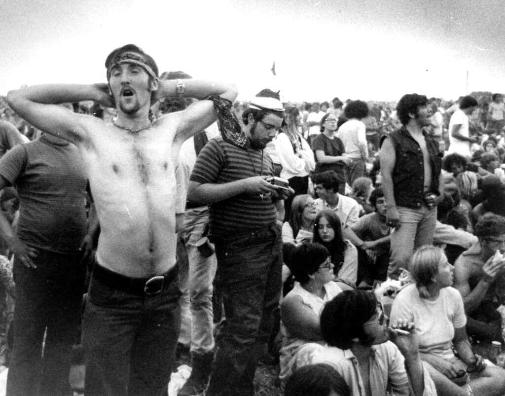 1969 file photo: Music fans on a break at Woodstock in Bethel, NY. The music festival will be celebrated on its 50th anniversary, but not as a hippie trample-the-fences kind of concert. (AP Photo)