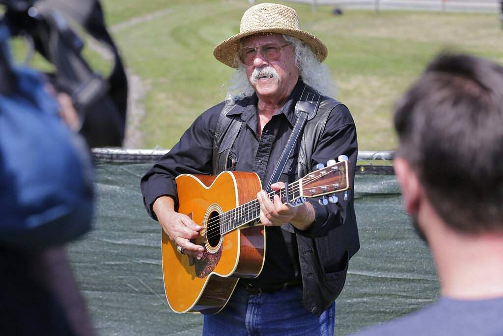 Woodstock veteran Arlo Guthrie plays a song at the original site of the 1969 Woodstock Music and Arts Fair in Bethel, NY, Thursday, Aug 15, 2019. (AP Photo/Seth Wenig)