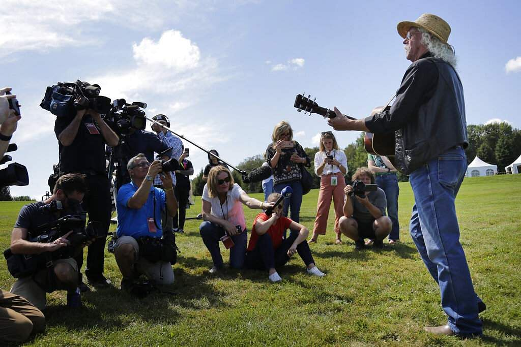 Members of the media record as Woodstock veteran Arlo Guthrie plays a song at the original site of the 1969 Woodstock Music and Arts Fair in Bethel, NY. (AP Photo/Seth Wenig)