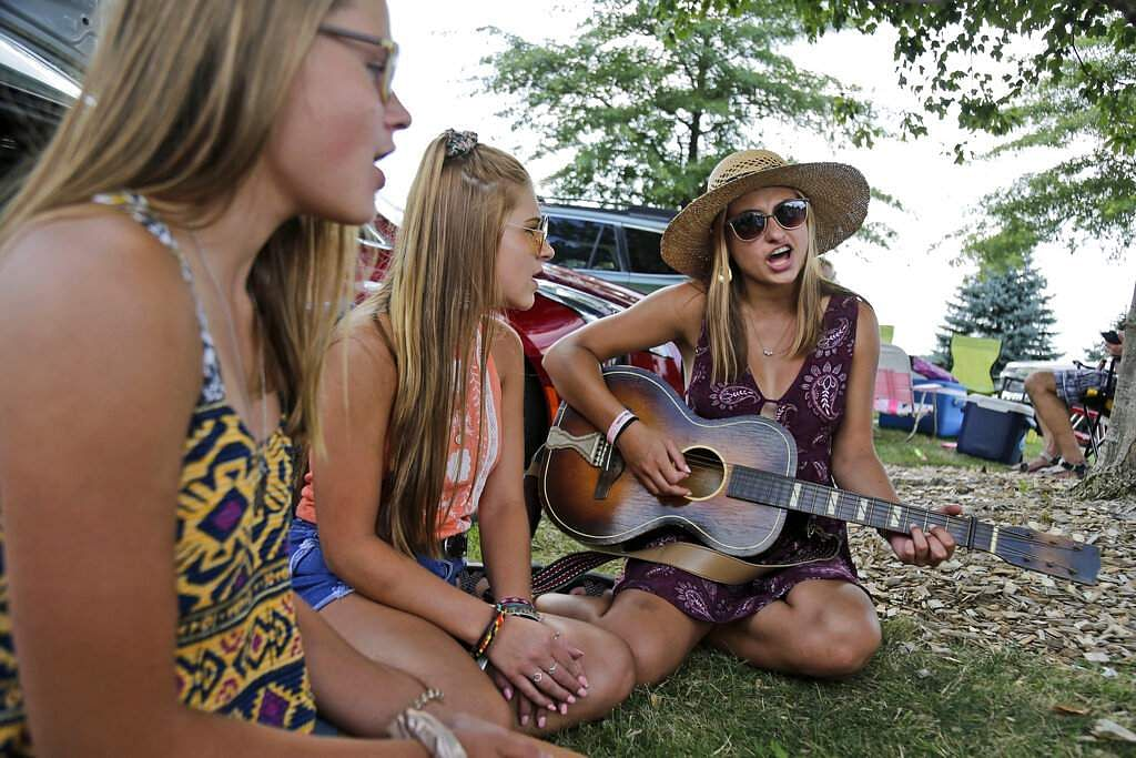 The Lescinski sisters, Kristi, 19, Jaime, 17 and Emily, 13, sing together in the parking lot waiting for the gates to open at a Woodstock 50th anniversary event. (AP Photo/Seth Wenig)