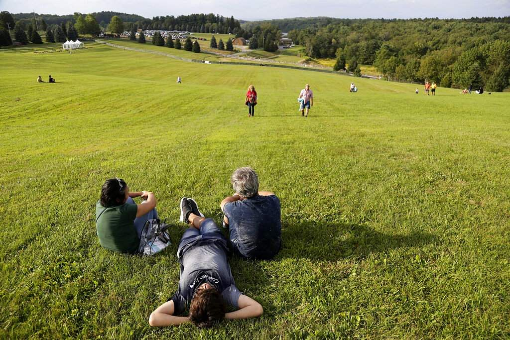 People walk and lie on the site of the original 1969 Woodstock Music and Arts Fair while waiting for the start of a 50th anniversary event nearby in Bethel, NY. (AP Photo/Seth Wenig)