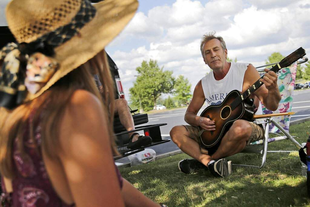Al Westphal sings and plays his guitar in the parking lot while while waiting for the gates to open at a Woodstock 50th anniversary event in Bethel, NY. (AP Photo/Seth Wenig)