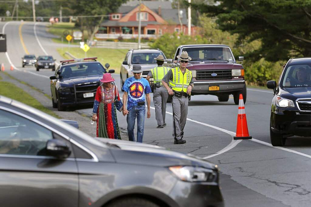 Officials direct light traffic at the entrance to Bethel Woods, the site of a Woodstock 50th anniversary event, in Bethel, NY, Thursday, Aug 15, 2019. (AP Photo/Seth Wenig)