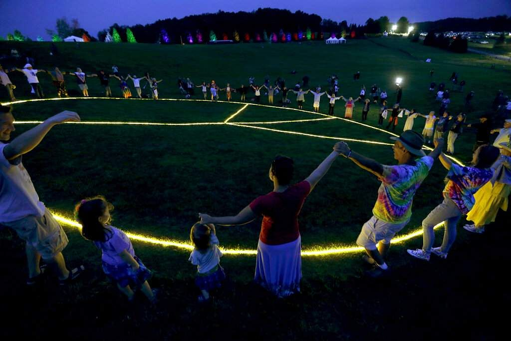 People hold hands in a circle around a large, illuminated peace sign on the original site of the 1969 Woodstock Music and Arts Fair in Bethel, NY, Thursday, Aug 15, 2019. (AP Photo/Seth Wenig)
