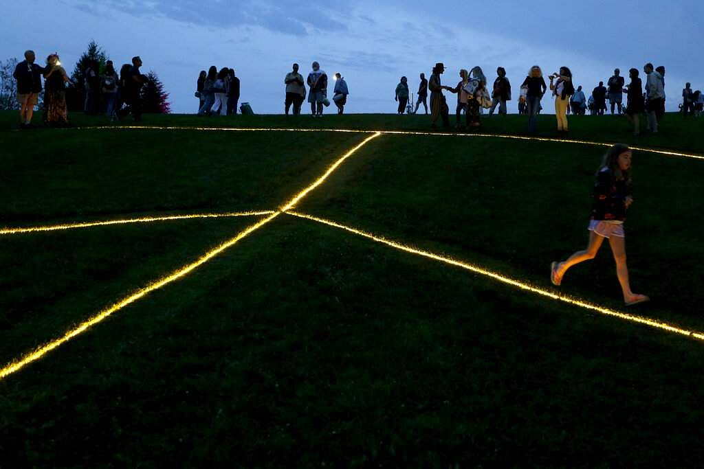 People gather around a large, illuminated peace sign on the original site of the 1969 Woodstock Music and Arts Fair in Bethel, NY, Thursday, Aug 15, 2019. (AP Photo/Seth Wenig)