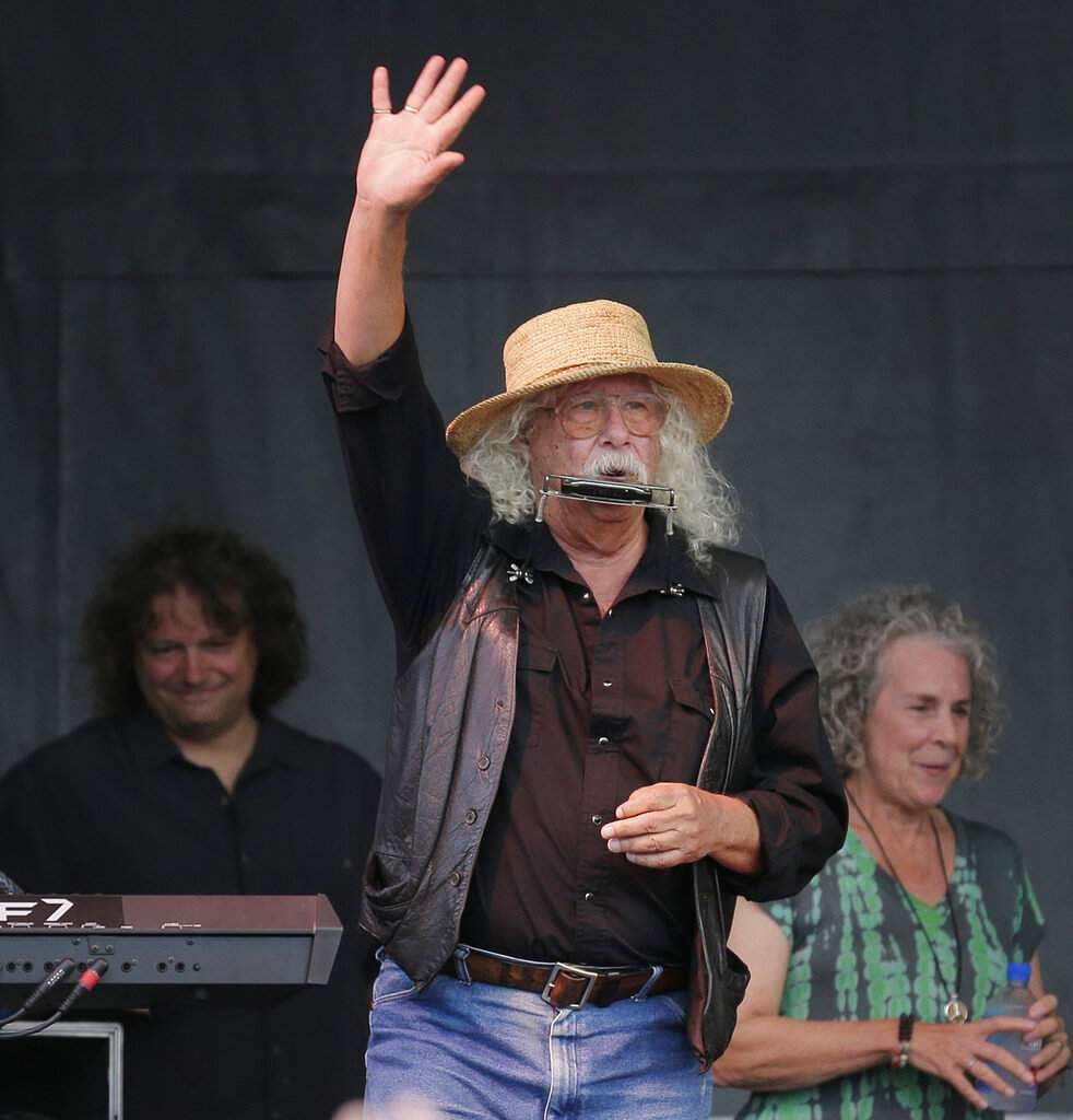 Arlo Guthrie waves to the crowd during a concert at a Woodstock 50th anniversary event in Bethel, NY, Thursday, Aug 15, 2019. (AP Photo/Seth Wenig)