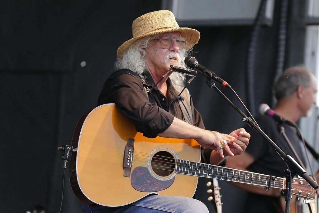 Arlo Guthrie talks during a concert at a Woodstock 50th anniversary event in Bethel, NY, Thursday, Aug 15, 2019. (AP Photo/Seth Wenig)