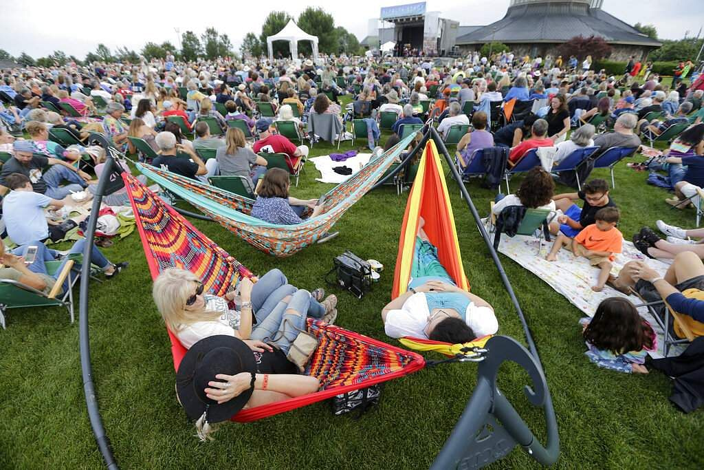 People enjoy a concert by Arlo Guthrie at a Woodstock 50th anniversary event in Bethel, NY, Thursday, Aug 15, 2019. (AP Photo/Seth Wenig)