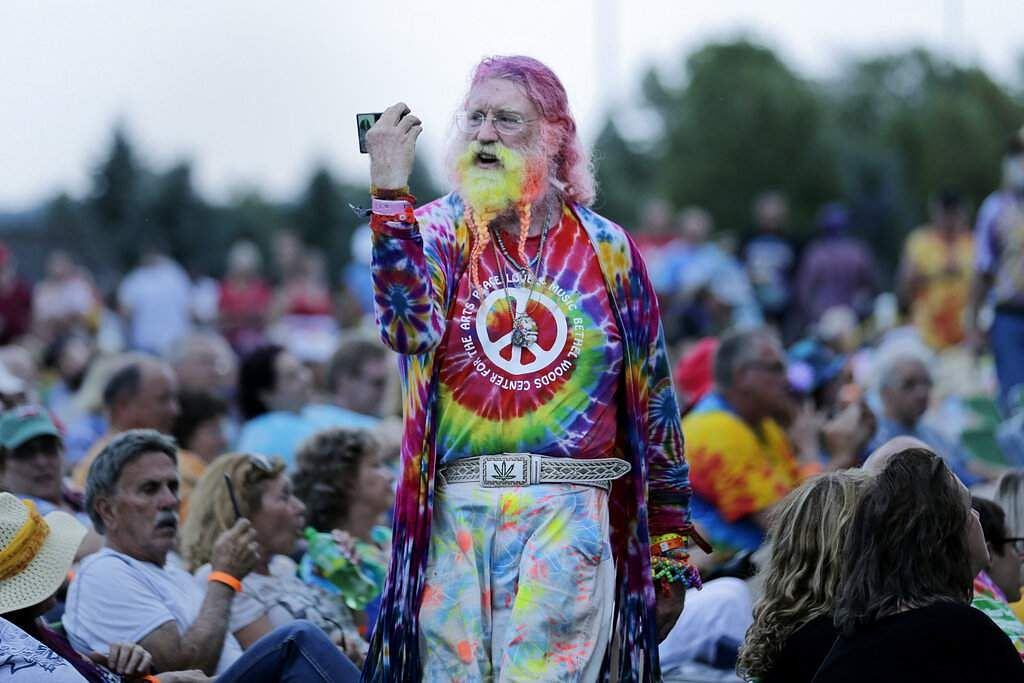 A man walks through the crowd during an Arlo Guthrie concert at a Woodstock 50th anniversary event in Bethel, NY, Thursday, Aug 15, 2019. (AP Photo/Seth Wenig)