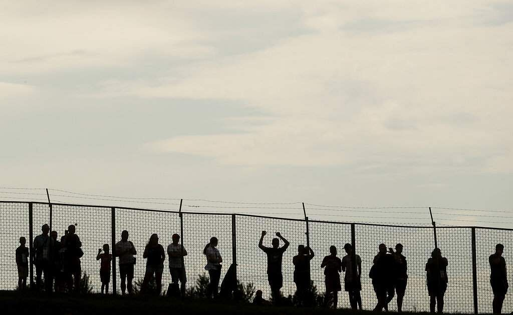 Spectators watch from behind a fence at the Hungaroring racetrack in Mogyorod, northeast of Budapest, Hungary. The Hungarian Formula One Grand Prix takes place on Sunday. (AP Photo/Laszlo Balogh)