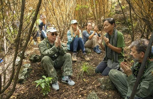 Paul Simon joins a prayer led by Aimee Sato, prior to planting a lama tree at Auwahi Forest Reserve on Maui, Hawaii, as part of a forest restoration effort. (Anna Kim/Honolulu Star-Advertiser via AP)