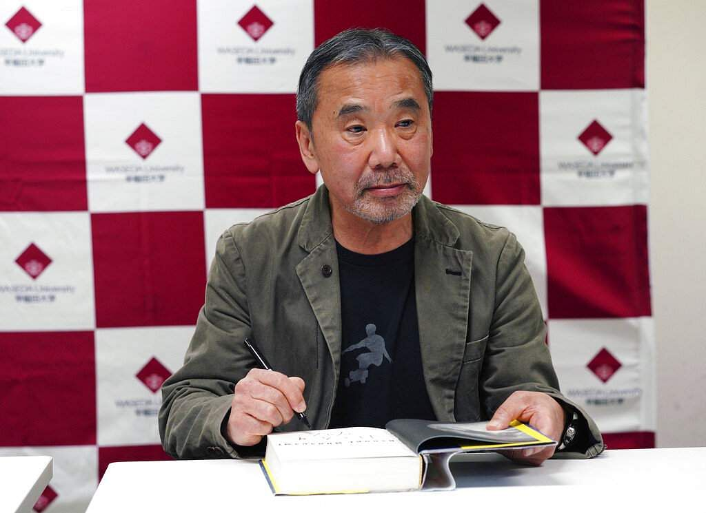 Haruki Murakami autographs a copy of Killing Commendatore. While people associate Japanese literature with male writers, things are changing with a wave of female writers. (AP Photo/Eugene Hoshiko)