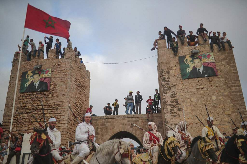 People watch atop an ancient wall as riders wait during Tabourida, a traditional horse riding show also known as Fantasia, in the coastal town of El Jadida, Morocco. (AP Photo/Mosa'ab Elshamy)