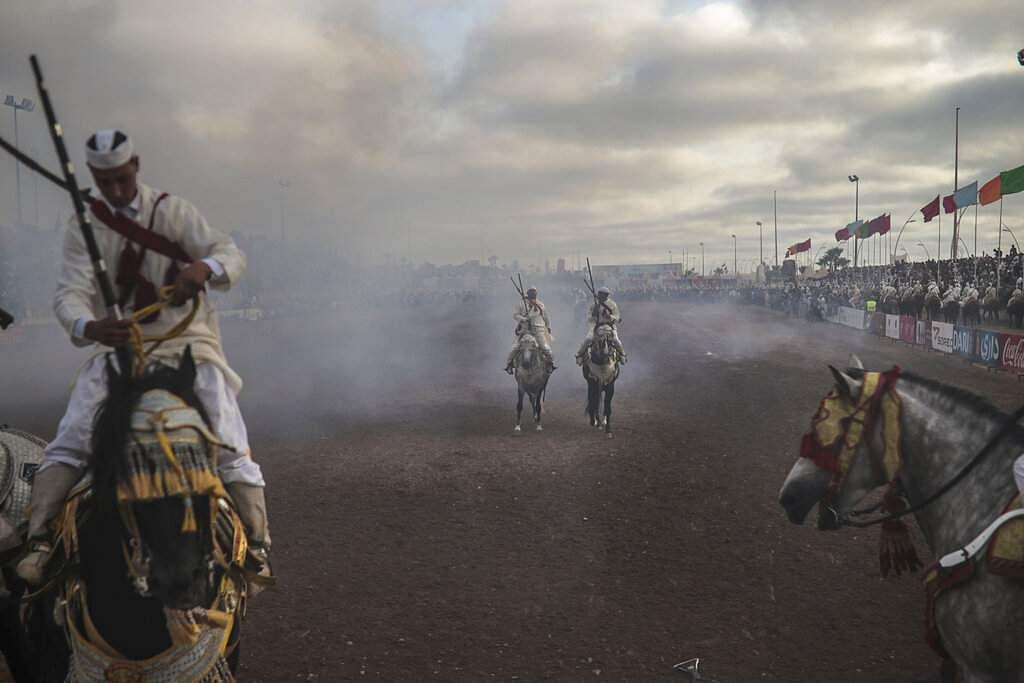 A troupe is engulfed by smoke after firing their rifles during Tabourida, a horse riding show also known as Fantasia, in the town of El Jadida, Morocco. (AP Photo/Mosa'ab Elshamy)